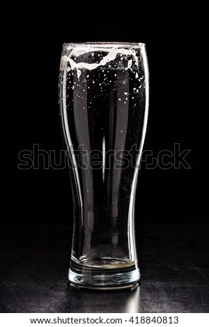 USED EMPTY Beer Glass with DROPS on black. FRESH! MUCH FOAM! Beer bubbles closeup. DRAFT. Overflow beer glass. Glass of alcohol. Closeup Cold Beer. Pint of beer. Good for brewery commercial - stock photo