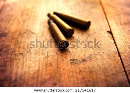 Used fire arm or rifle bullet cartridges on a old wooden floor.  - stock photo