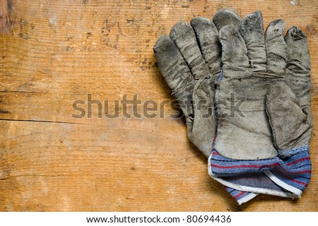 used gloves on wooden background - stock photo