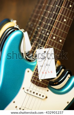 Used guitars at a instrument shop. Electric guitars on a guitar display stand with sale tag. Blue electric guitar in front. - stock photo