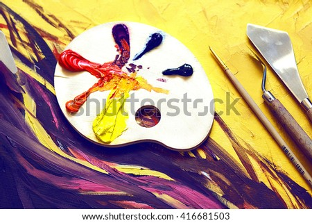 Used paint brushes on a colorful painter palette - stock photo