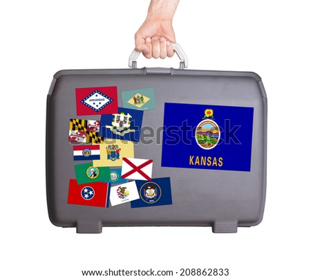 Used plastic suitcase with stains and scratches, stickers of US States, Kansas - stock photo