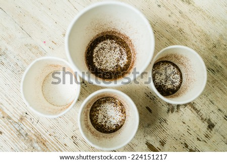 Used testing plastic cups with coffee grounds on the grunge wooden desk. View from above. Selecting and tasting coffee at laboratory. Selective focus. - stock photo