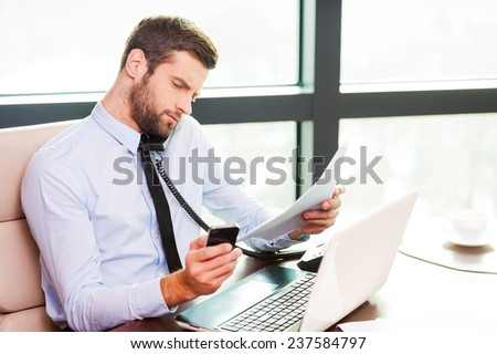 Used to multi-tasking. Concentrated young man in shirt and tie talking on the phone and holding documents while sitting at his working place - stock photo