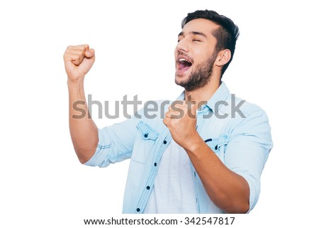 Used to win. Happy young Indian man gesturing and smiling while keeping eyes closed and standing against white background - stock photo