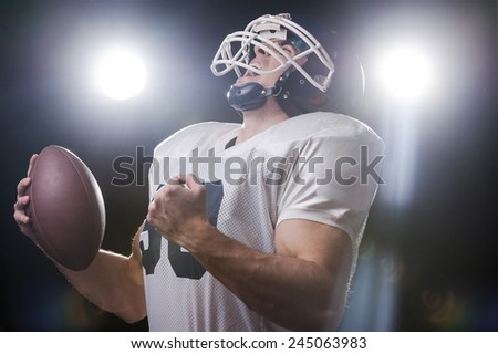 Used to win.  Portrait of American football player holding ball and screaming while standing against lights - stock photo