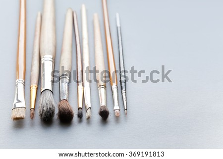 Used, vintage paintbrushes on gray background. macro view different size wooden and textured paint brush, shallow depth of field photography. copy space - stock photo