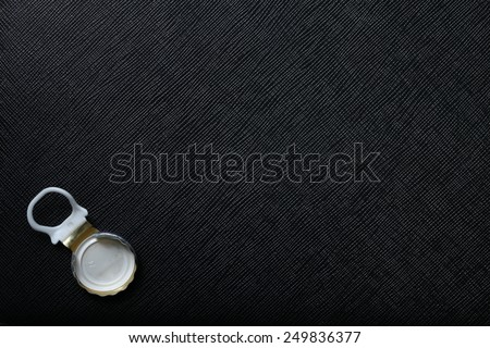 Used water bottle cap pulling type made from aluminum put on the black color leather background represent the beverage containing equipment related. - stock photo