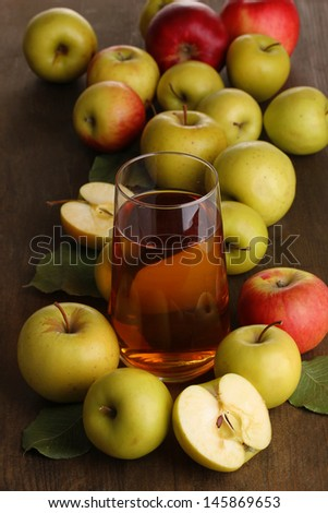 Useful apple juice with apples around on wooden table - stock photo