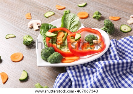 Useful cut vegetables on a plate in the form of heart on wooden table top view - stock photo