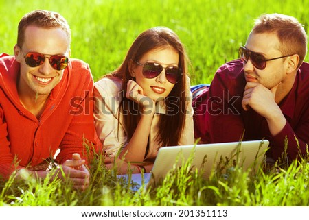 Useful weekend concept. Three happy friends having fun in the autumn park, lying together in green grass and using laptop. Trendy casual clothing and stylish eyewear. Shiny weather. Outdoor shot - stock photo