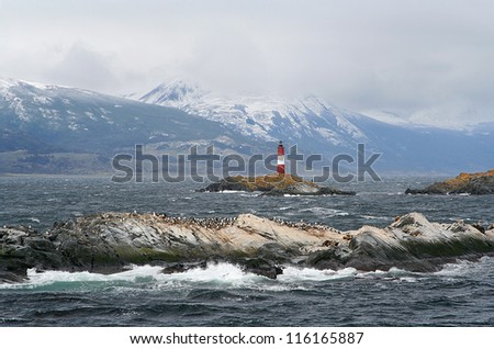 ushuaia lighthouse, called the world ends lighthouse, surrounded by islands full of cormorant birds - stock photo