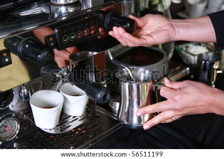 Using a coffee machine to make frothy milk for a cappuccino - stock photo