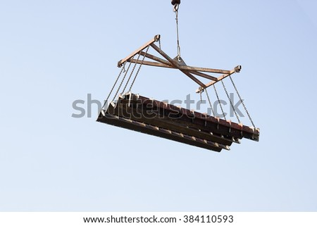 Using a crane lifting a steel columns - stock photo