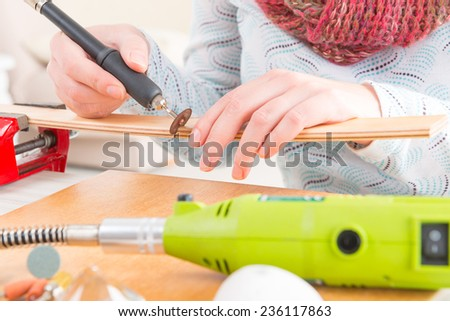 Using a high speed rotary multi tool to cut a wooden batten - stock photo