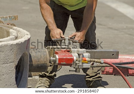 Using a hydraulic hole saw to cut in a large pipe into concrete new water line project with diamond bit or saw - stock photo