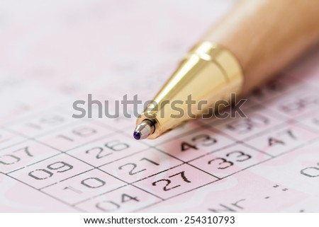 Using a pen to fill out a lottery slip to play the lotto - stock photo