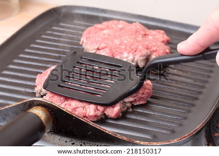 Using a spatula to cook burgers on a grill-pan - stock photo