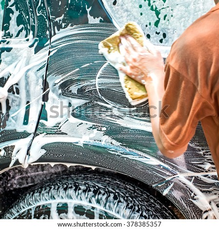 Using a sponge for cleaning car - stock photo
