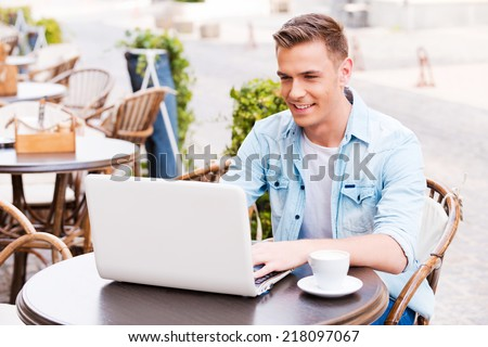 Using advantages of free Wi-Fi. Handsome young man working on laptop and smiling while sitting in sidewalk cafe - stock photo