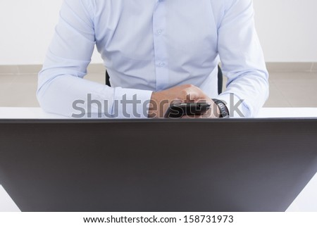 Using cellphone and laptop in office - stock photo
