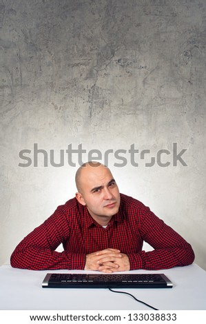 Using computer. Man sitting at the table with keyboard in front of the computer - stock photo