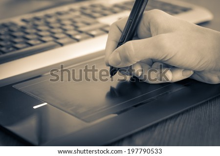Using graphic tablet with PC. Toned image - stock photo