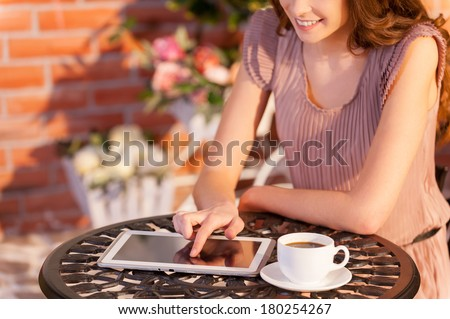 Using her brand new tablet in cafe. Cropped image of woman working on digital tablet while sitting at the outdoor cafe - stock photo
