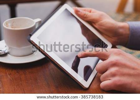 using internet on tablet in cafe, checking email and social networks on touchpad, closeup of finger - stock photo