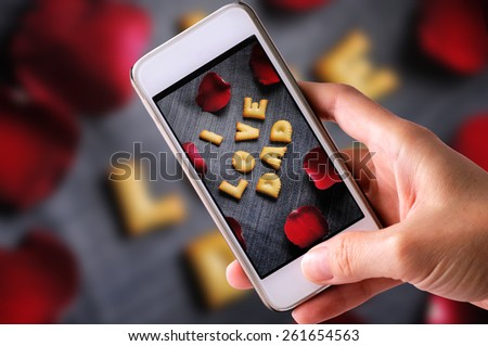 using mobile phone to take photos of Cookies ABC in the form of word I LOVE DAD alphabet with red rose petal on old jean background, Valentines day - stock photo