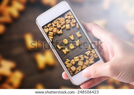 using mobile phone to take photos of Cookies ABC in the form of word LOVE MOM alphabet with sunbeams and lens flare on old wood background, Valentines day - stock photo
