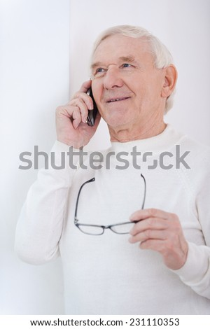 Using modern gadgets. Cheerful senior man talking on the mobile phone and holding glasses while leaning at the wall - stock photo