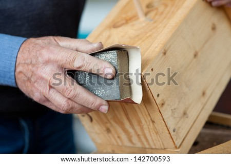 Using sandpaper for polishing birdhouse at worktable in workshop - stock photo