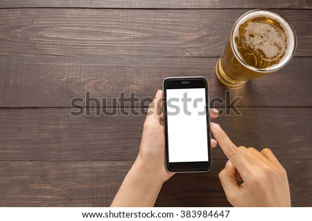 Using smartphone beside of beer in the pub. - stock photo