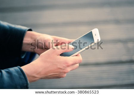 Using smartphone outdoors. Focus on the hands with phone - stock photo