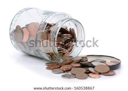 using the rainy day fund, coins spilling out of a jar - stock photo