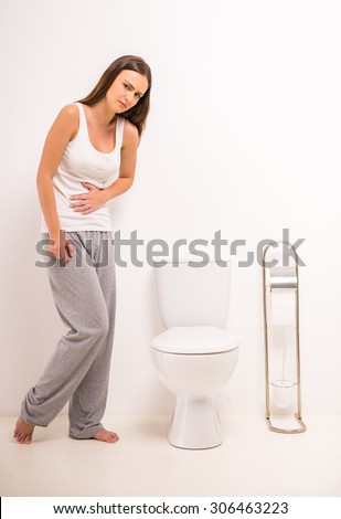 Using toilet. A young woman uses a toilet with a roll of toilet paper in his hand. - stock photo