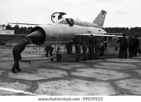 USSR - CIRCA 1976:  Mechanics roll aircraft MiG-21 on parking, air base Kubinka, Moscow Region, USSR, July 1976 - stock photo