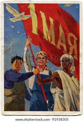 USSR  - CIRCA 1959: Postcard printed in the USSR honoring 1st of May shows three nationalities workers with a red flag in his hands, circa 1959 - stock photo