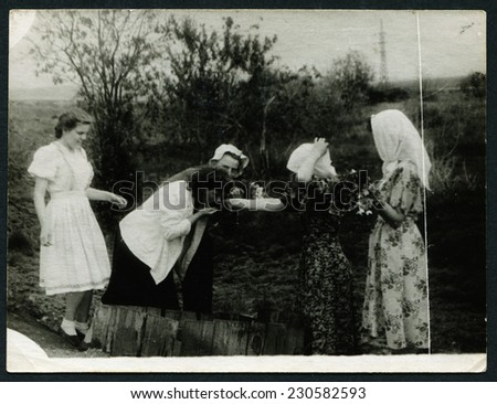USSR - CIRCA 1950s: An antique photo shows woman drinking water from a well - stock photo