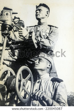 USSR - CIRCA 1940s: Two Soviet soldiers firing anti-aircraft guns. USSR, 1940s. Reproduction of antique photo. - stock photo