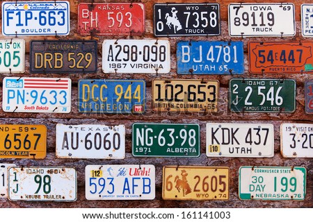 UTAH, USA - NOVEMBER 16: Various old American license plates behind antique gas pump on November 16, 2008. License plates are from various American states. - stock photo