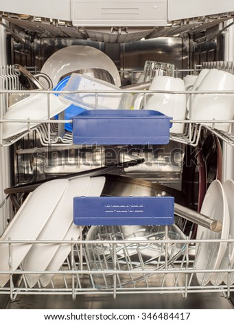 Utensils in dishwasher, washed cups and plates - stock photo