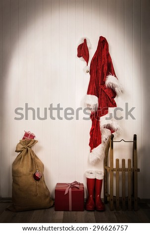Utensils of santa clause - jacket, hat, boots, sack and sledge. Wooden vintage christmas background with gifts in red and white. - stock photo
