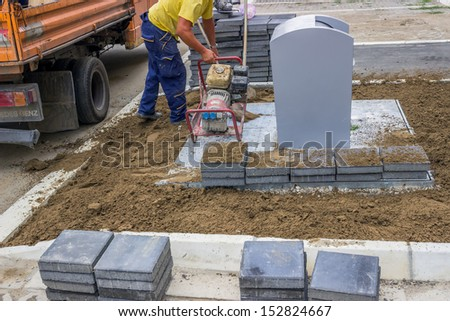 Utility crew works. Preparation for paving around the underground containers, with paving stone at urban place. - stock photo