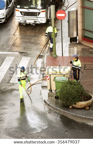 utility service company men workers cleaning the street with water pressure at city - stock photo