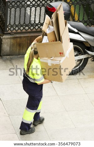 utility service company woman  worker  of  municipality collected cartons for recycling in street city - stock photo
