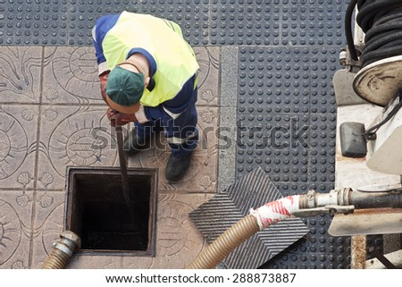 utility service company  worker  moves the manhole cover to cleaning the sewer line for clogs - stock photo