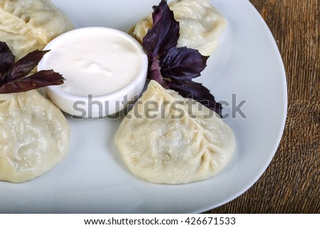 Uzbek dumplings with sauce and basil leaves - stock photo