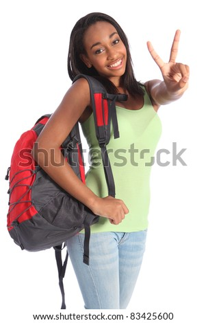 V for victory success by pretty young African American teenager school girl, with long black hair wearing green t-shirt and red school backpack with beautiful smile. - stock photo